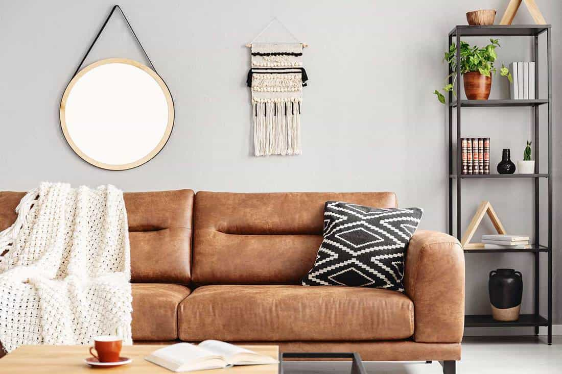 Bright living room interior with brown leather sofa and metal rack with decor and books