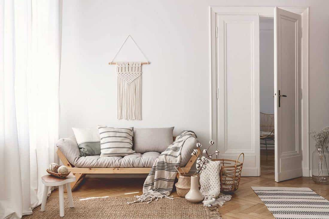 Bright living room interior with stylish macrame, sofa, wooden accessories and doors open to next room