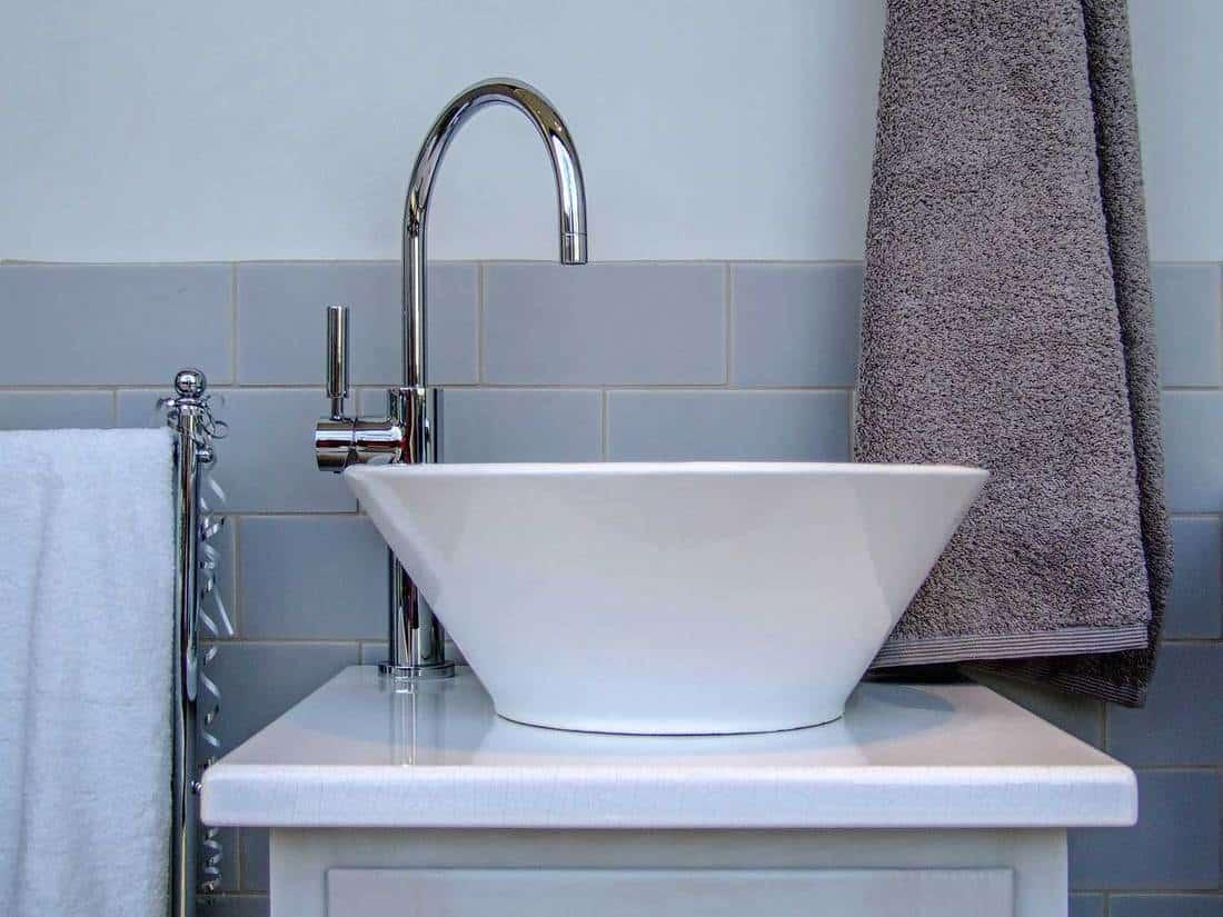 Ceramic bathroom sink in modern toilet with grey towel