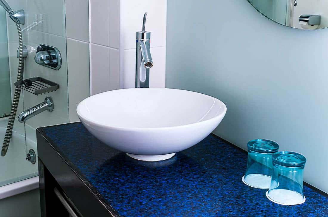 Ceramic bathroom sink with dark blue countertop
