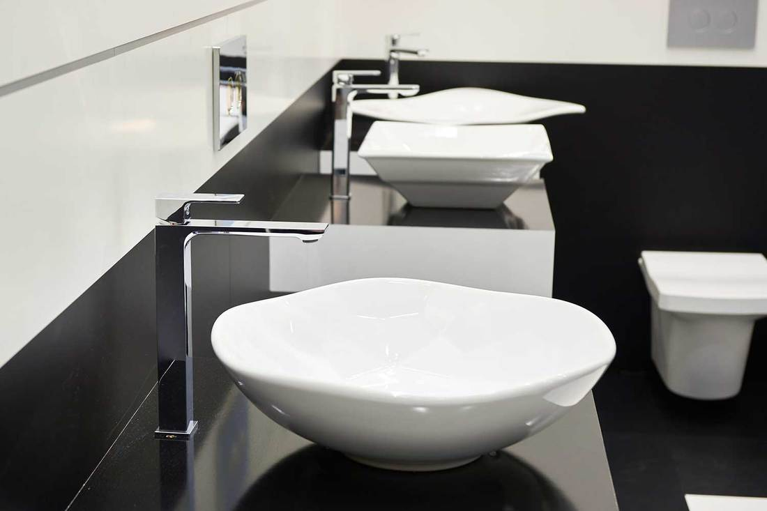 Ceramic sink with faucets in public toilet