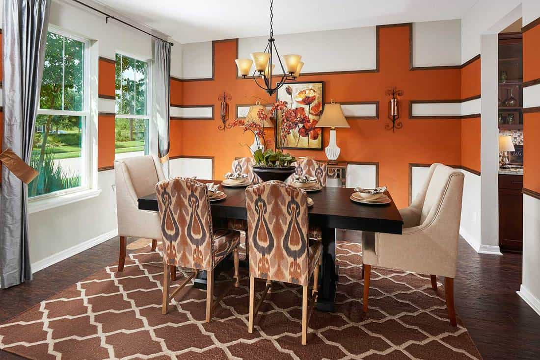 Classic dining room interior in a modern house with an intricate accent wall, brown carpet and hardwood floor