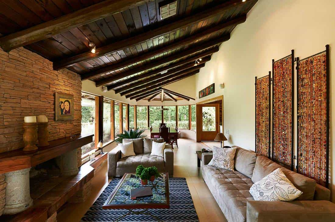 Classic rustic living room interior design with fireplace, sofa set, tiled floors and glass windows