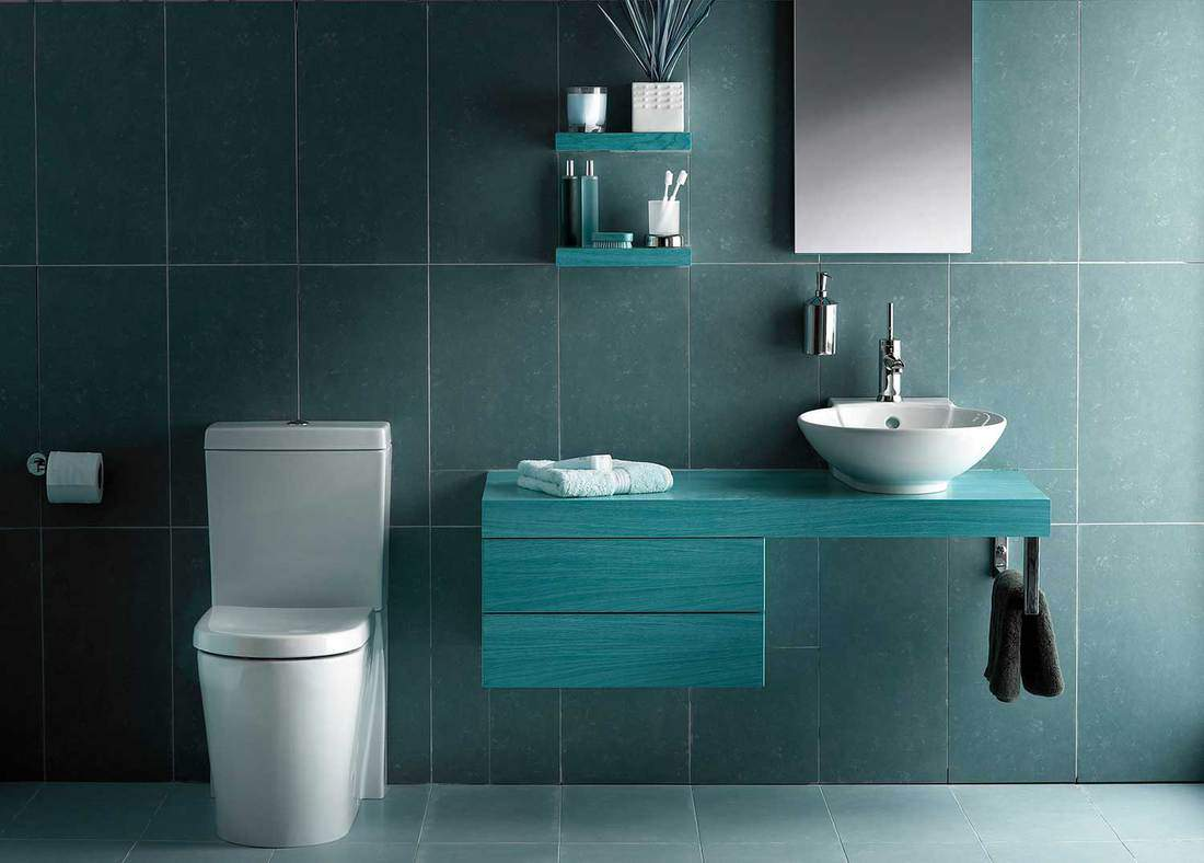 Cold tone modern bathroom with toilet, sink on wooden countertop and mirror