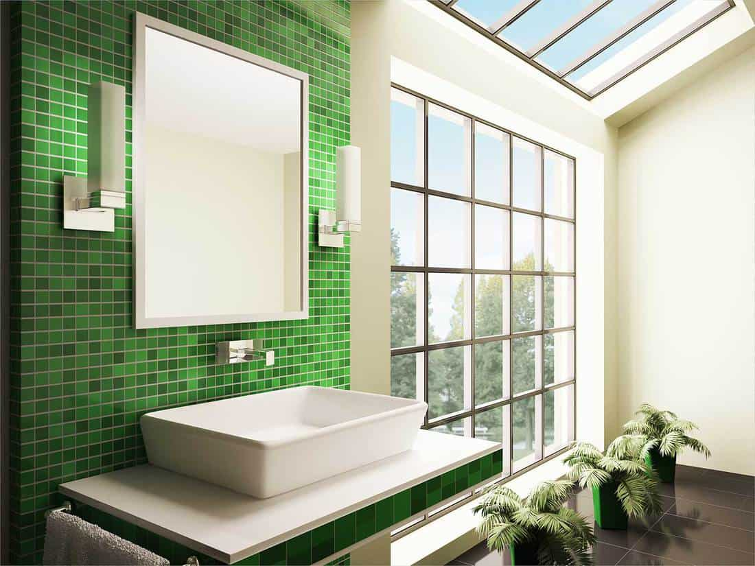 Contemporary bathroom interior with green tiles and window