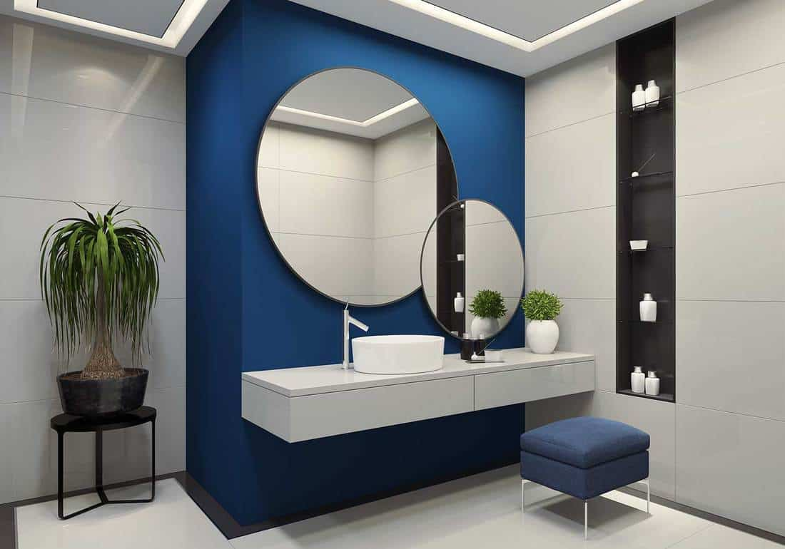 Contemporary blue and white bathroom with two round mirrors with black frames on royal blue wall
