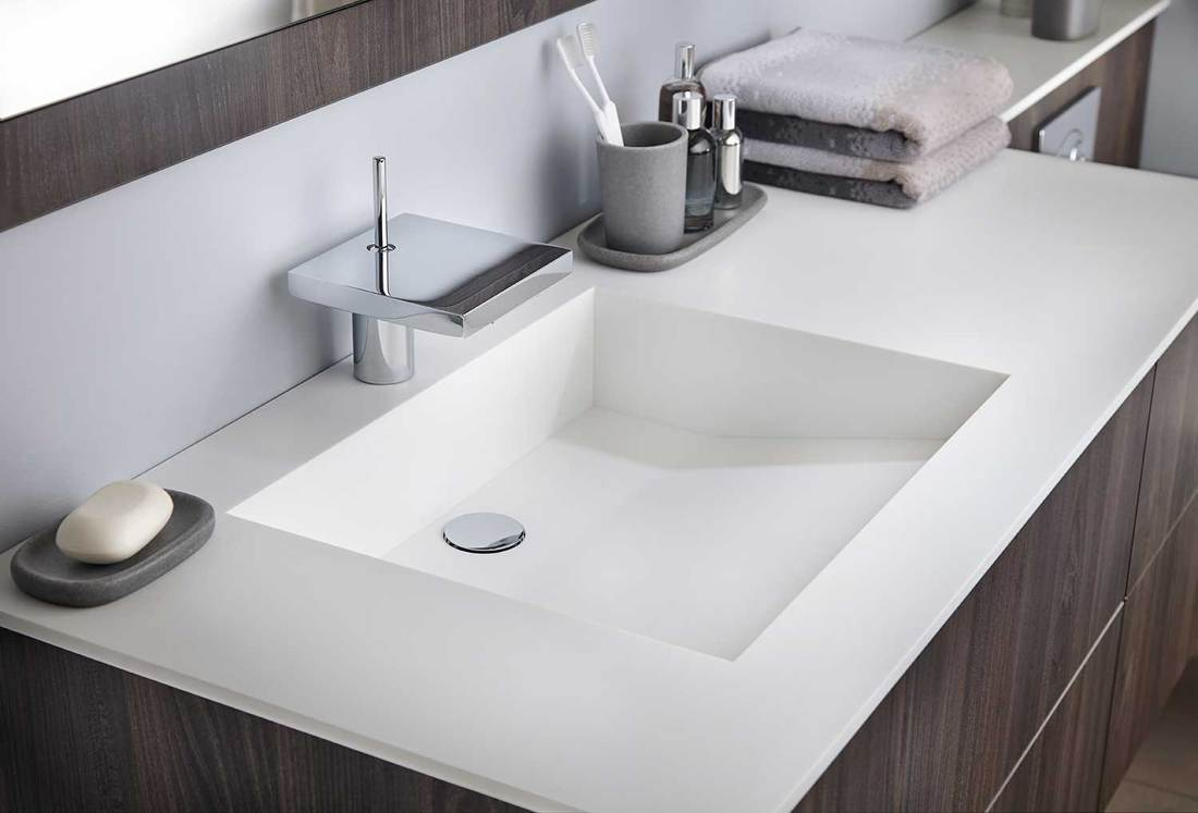 Contemporary designed bathroom sink with wood cabinets, toothbrush, towels and soap
