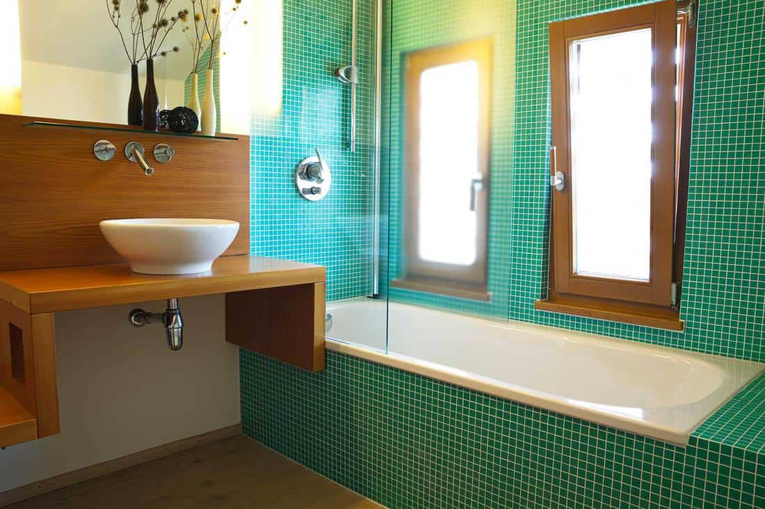 Contemporary house bathroom with green tiles, bathtub, modern sink and faucet