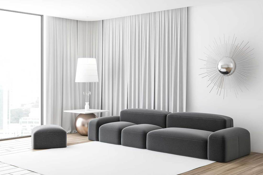 Corner of modern living room with white walls, large windows with white curtains, gray sofa and stylish wall decoration