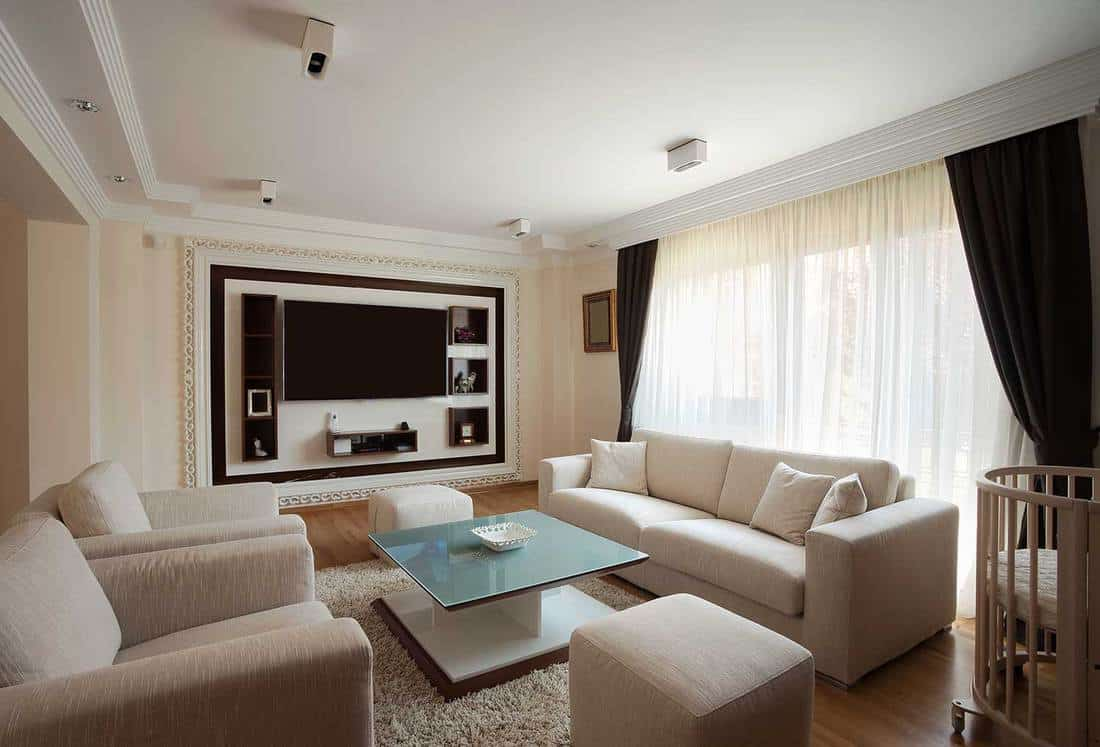 Cozy bright modern living room interior with TV, parquet floor, large glass windows and baby crib