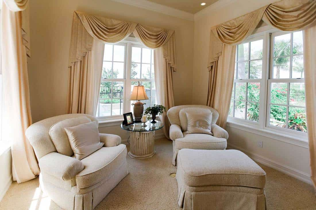 Cozy neutral den with garden view windows
