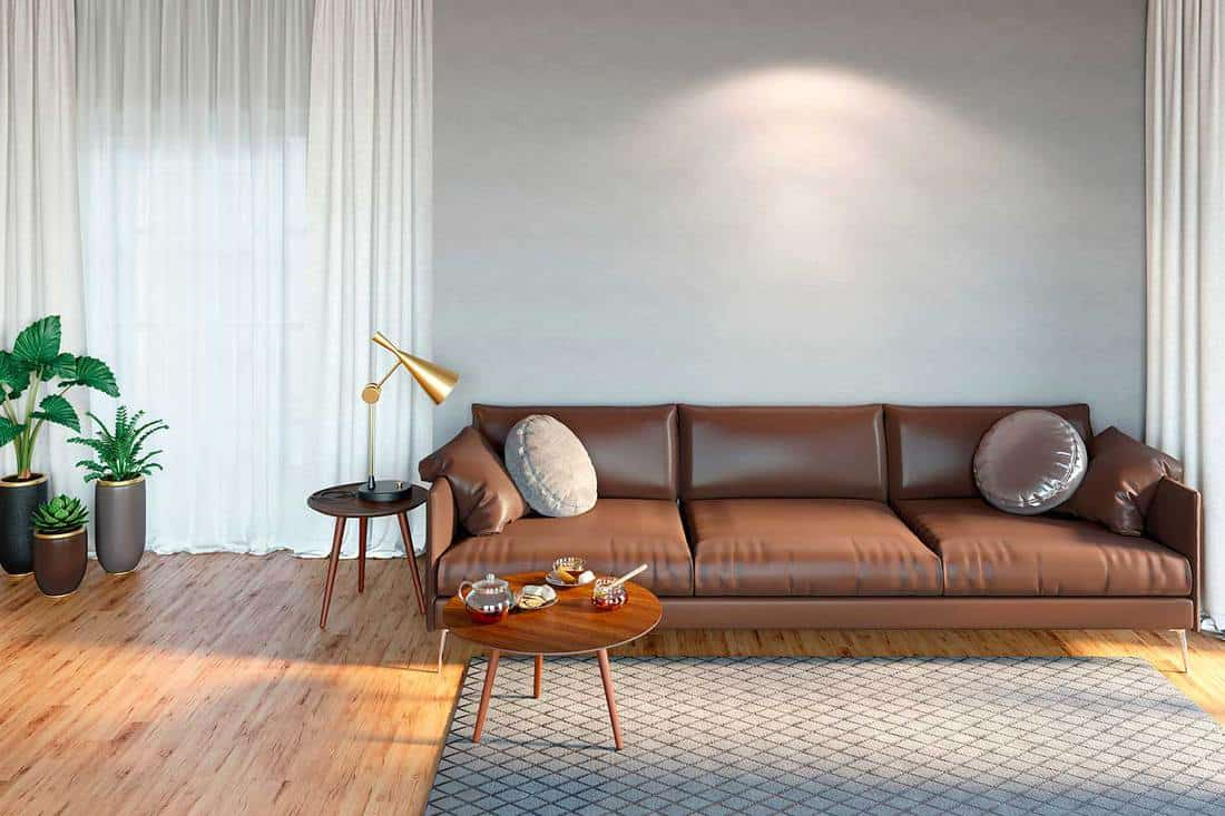 Cozy room interior with a leather sofa, a coffee table with a teapot and honey