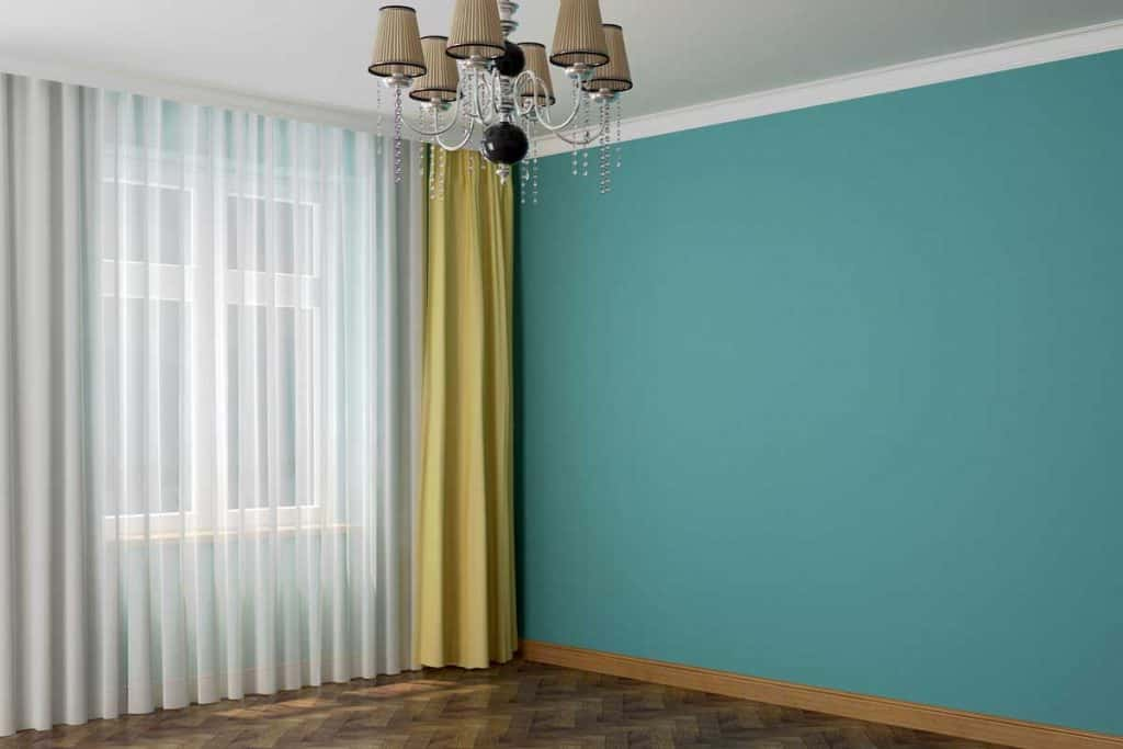 Bluish green colored wall with white and yellow curtains