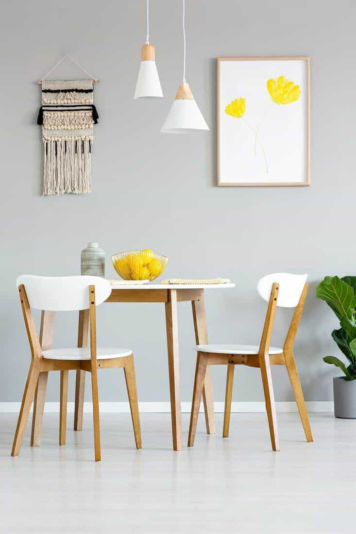 Dining room interior with poster of yellow flowers, round wooden table with matching chairs