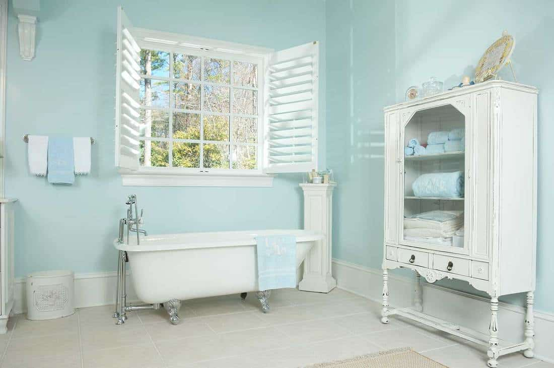 Domestic bathroom interior with wooden cabinet, bathtub and window on a sunny day