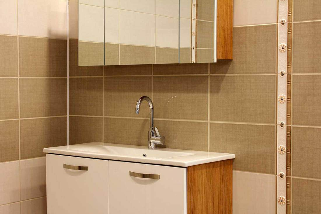Domestic bathroom sink with white cabinets and mirror above