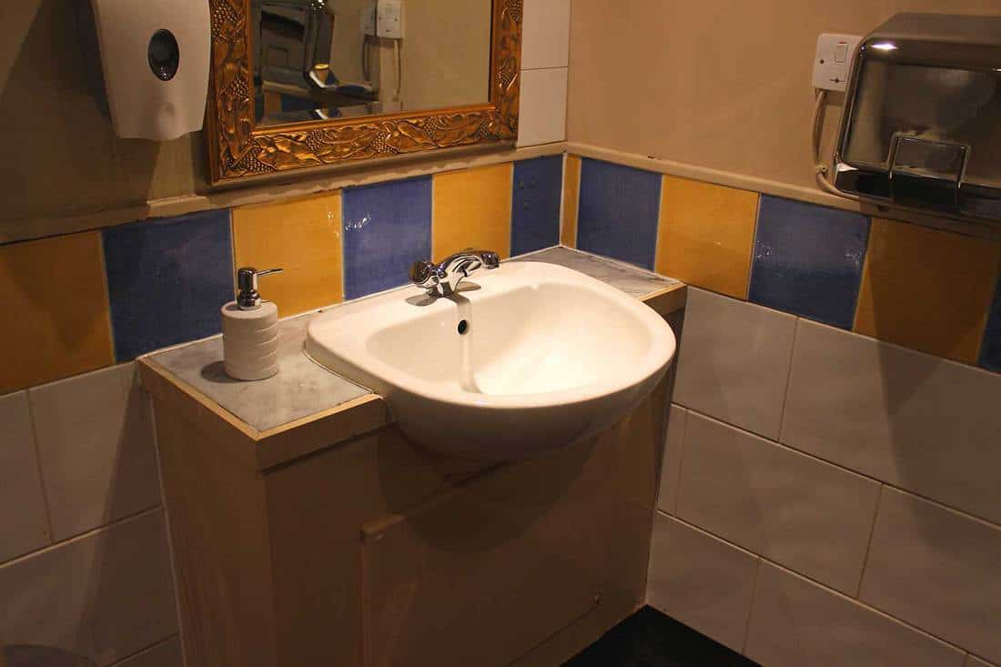 Domestic sink basin and storage cupboard in a toilet decorated with colourful blue and yellow tiles, a large mirror and hand dryer