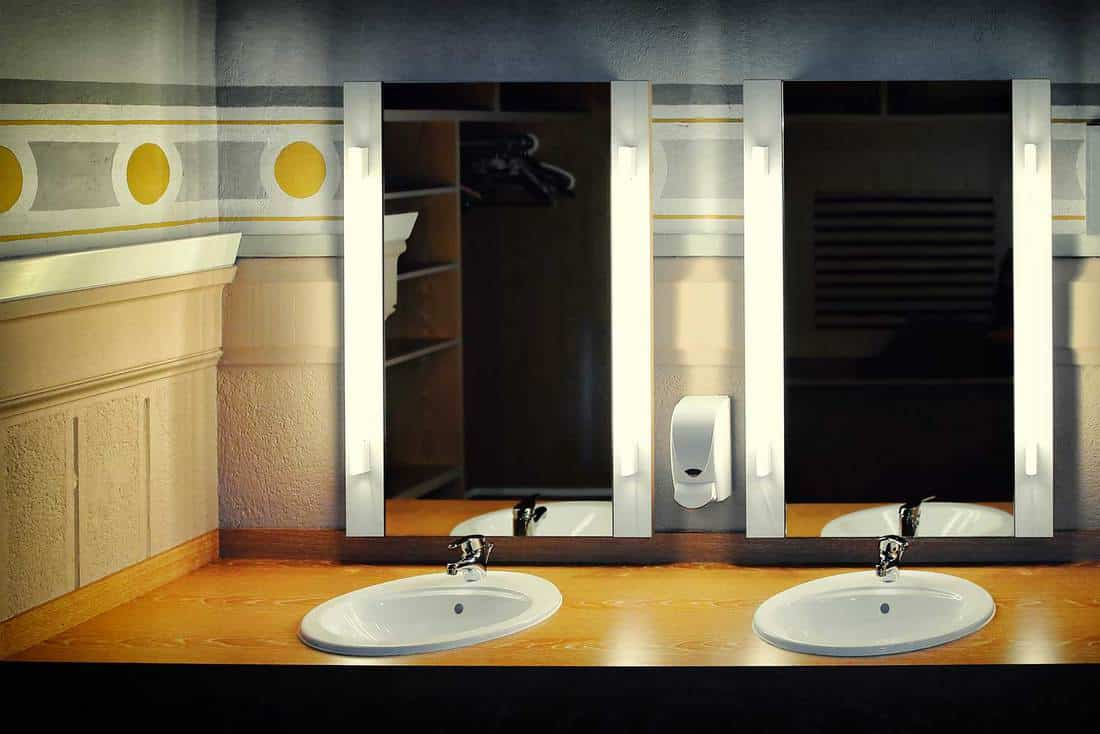 Empty bathroom with two sinks and large mirror