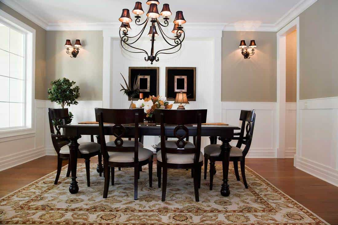 Formal dining room interior with carpet on parquet floor and elegant dining set