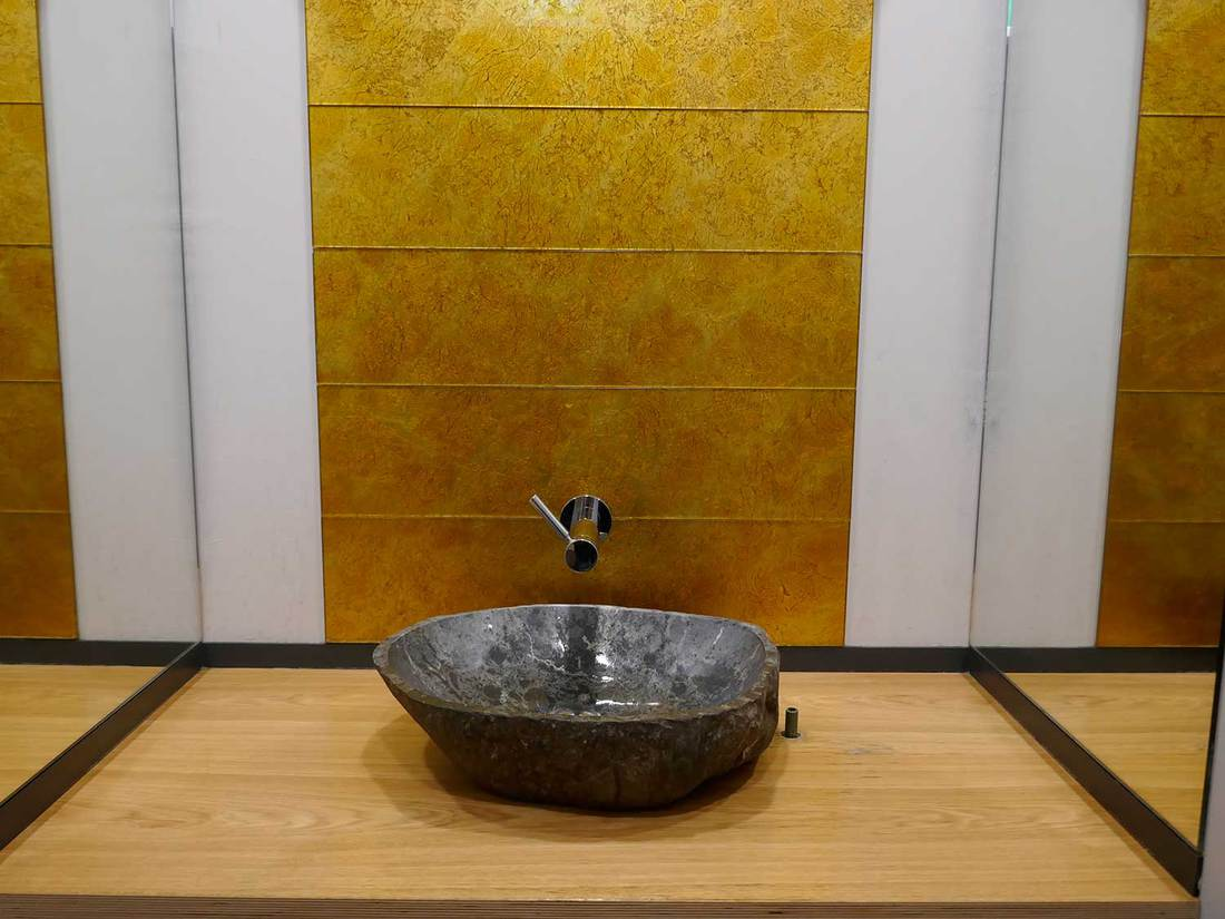 Grey natural stone wash basin on a wood washstand in front of golden shining textured wall