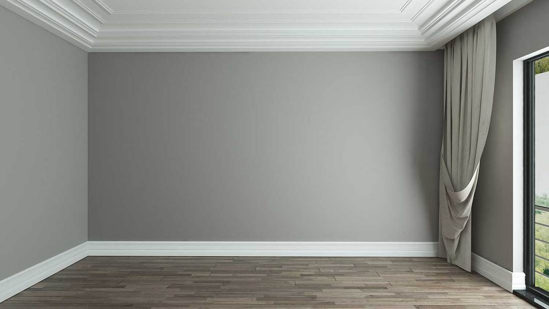 Grey wall, parquet floor and window with curtain in an empty room