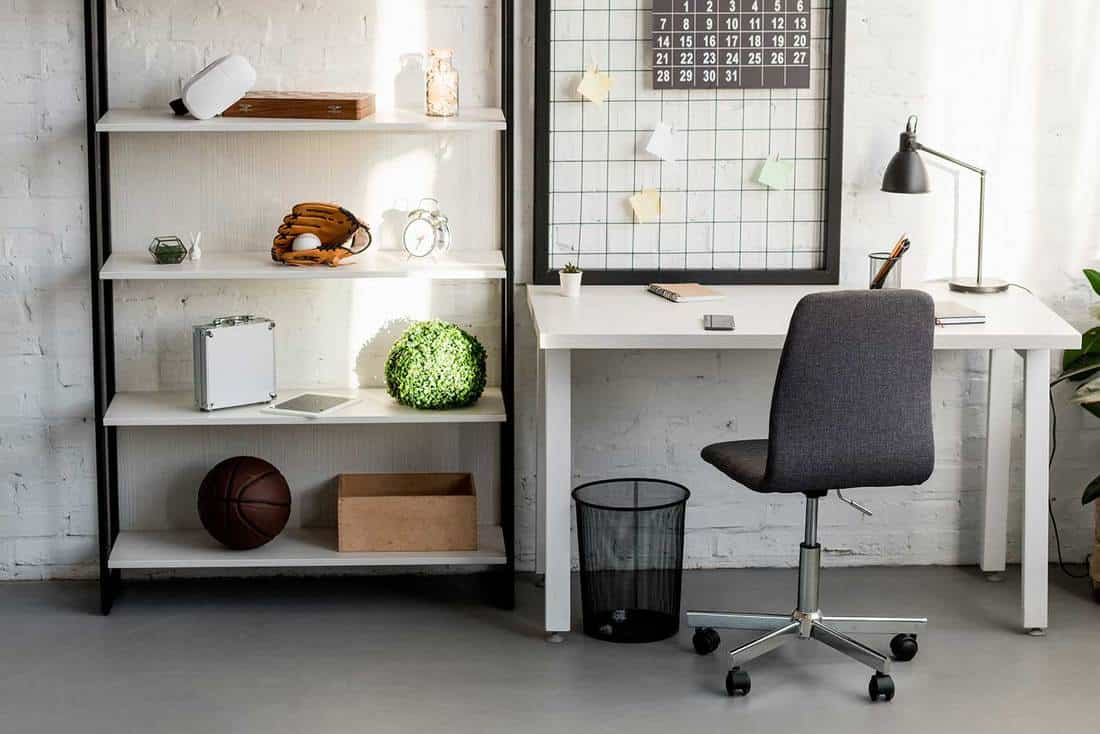 Home office interior with white brick walls, shelf rack and white study table