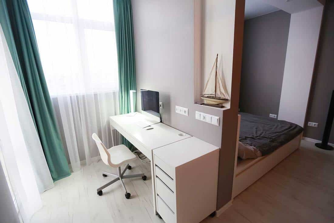 Interior of a compact smart apartment with walls divided into areas for work and recreation