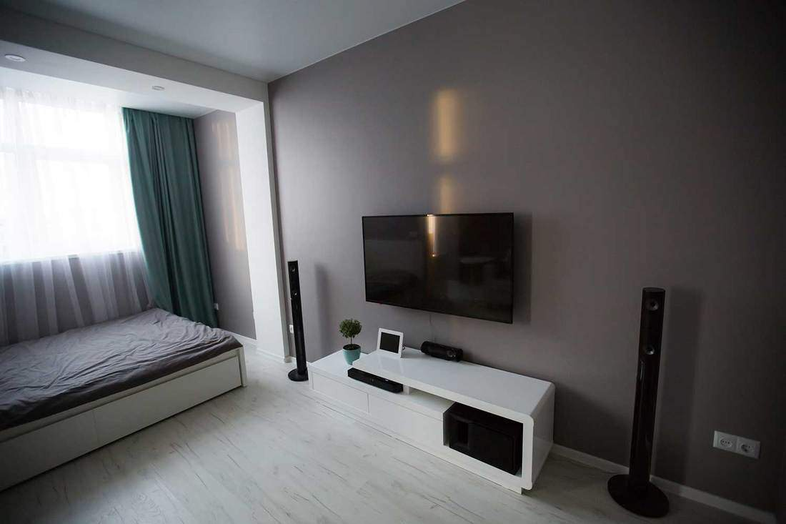 Interior of a modern studio type apartment with single bed and tv