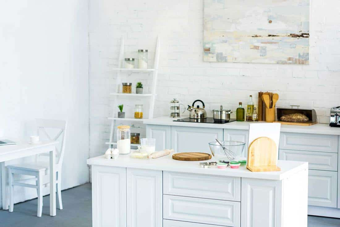 Interior of bright modern kitchen with painting on wall