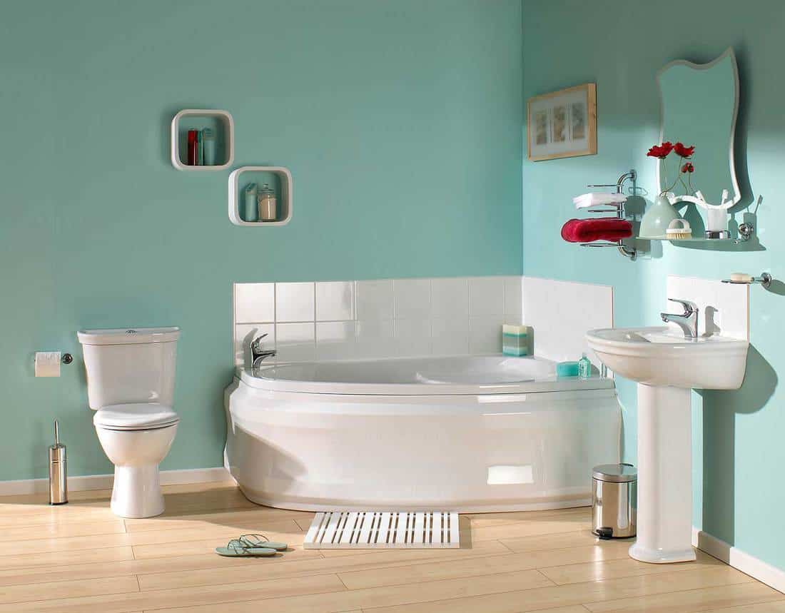 Interior of large modern bathroom with corner tub in pastel green