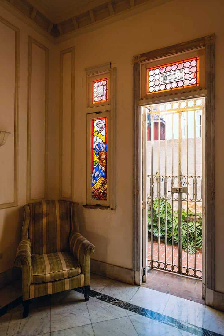 Iron bar door with old rustic stained glass windows in an old Havana villa