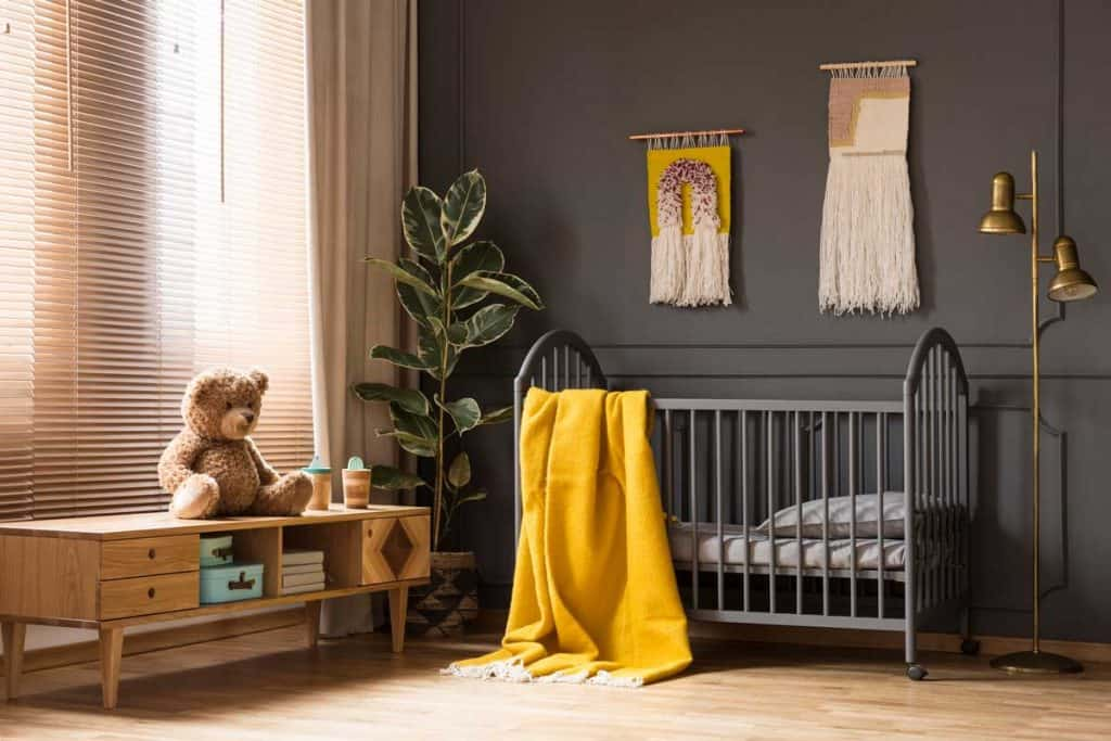 grey baby crib with matching grey was and light brown curtains