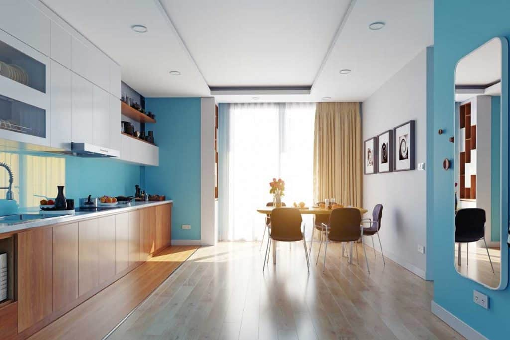 Modern kitchen interior with blue colored walls and wooden panel flooring