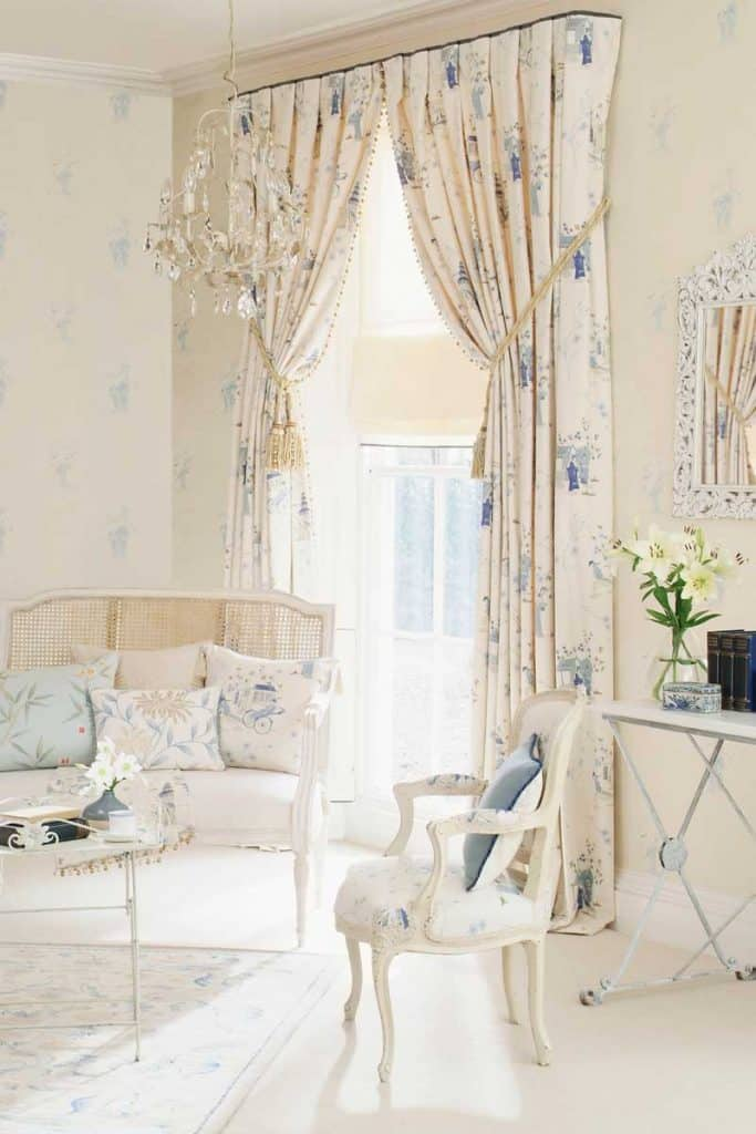 White couch with matching floral white curtains near chandelier