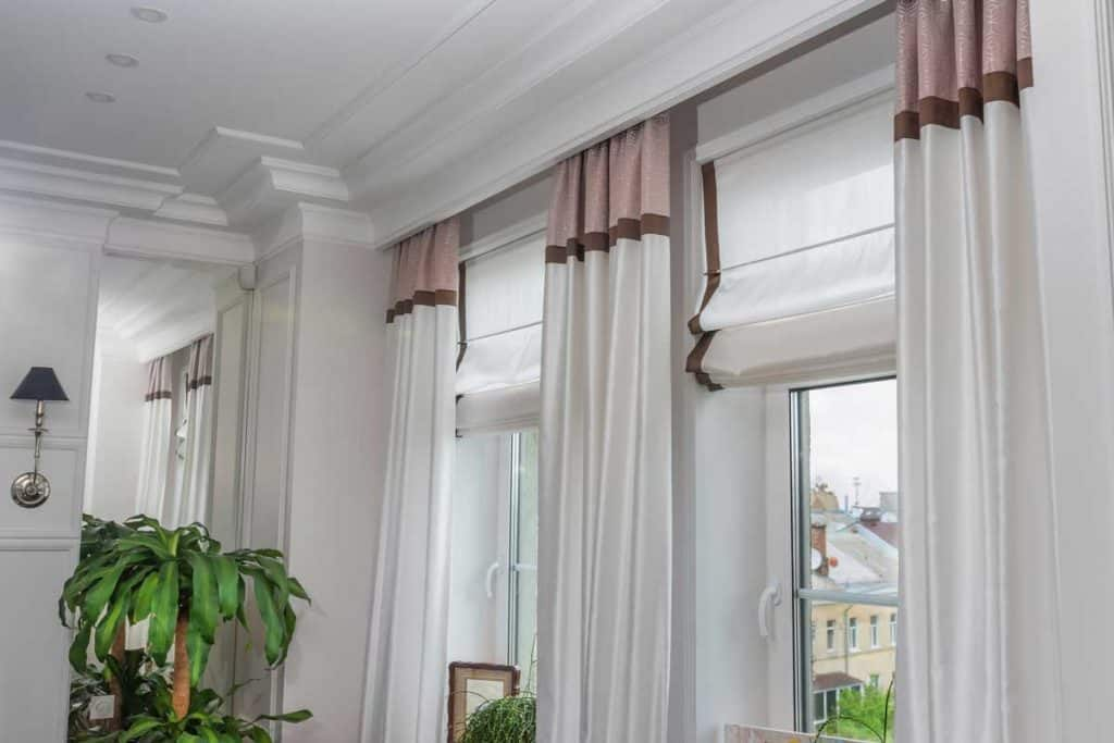 Off-white curtains, white walls with matching fortune plant and wall lamp