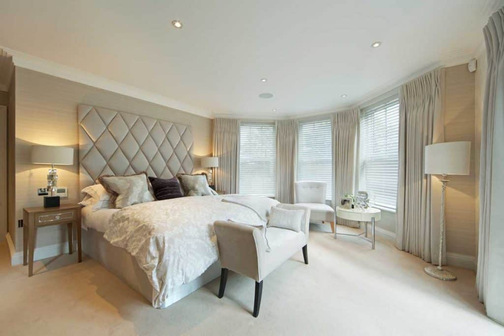 White walled masters bedroom with huge windows and white drapes