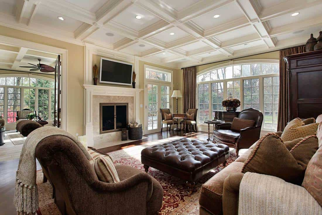 Large classic family room with fireplace, TV, cozy sofa and wall of windows