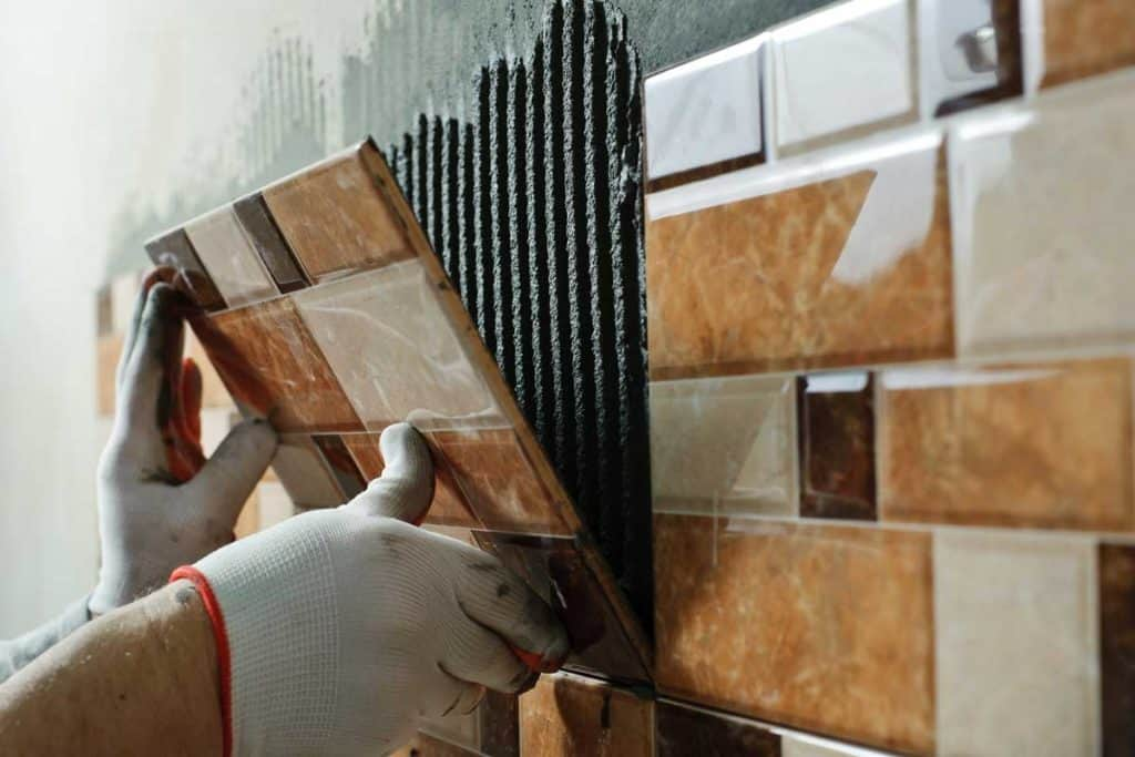 Laying-Ceramic-Tiles.-Tiler-placing-ceramic-wall-tile-in-position-over-adhesive