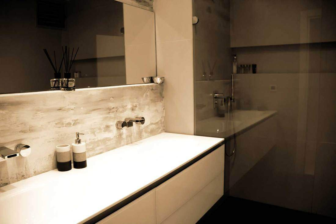 Lights off luxury bathroom with two faucet on large sink, shower and large mirror