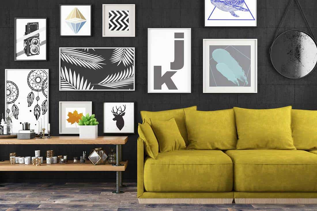 Living room interior with cozy yellow sofa, coffee table, parquet floor and graphic art decors on black wall