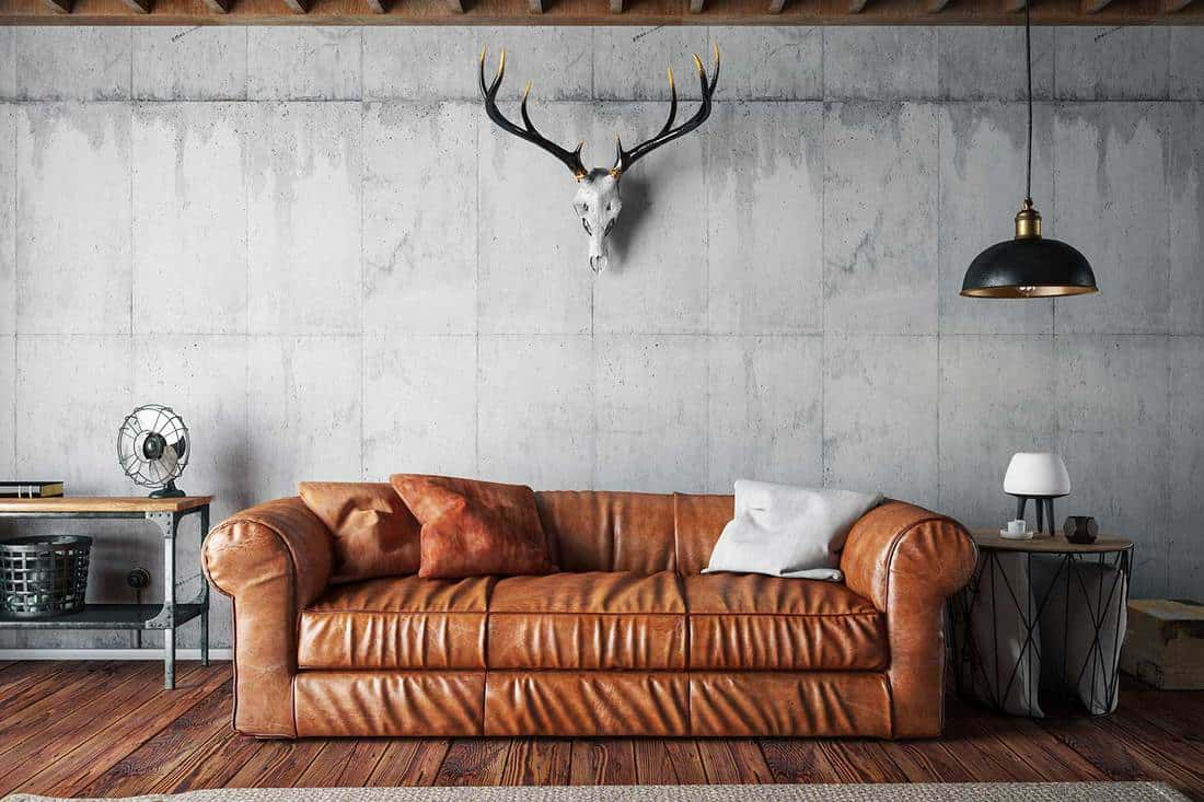 Loft interior living room with leather sofa and deer skull