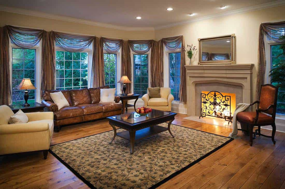 Lovely stylish well appointed living room with burning fireplace, elegant curtains and hardwood floors