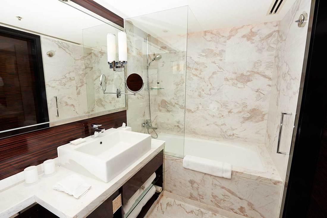 Luxury bathroom with marble walls, bathtub, shower and white ceramic sink