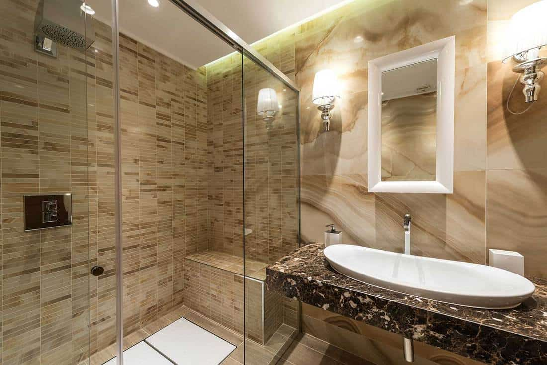 Luxury decorated bathroom, glass shower, large sink and mirror