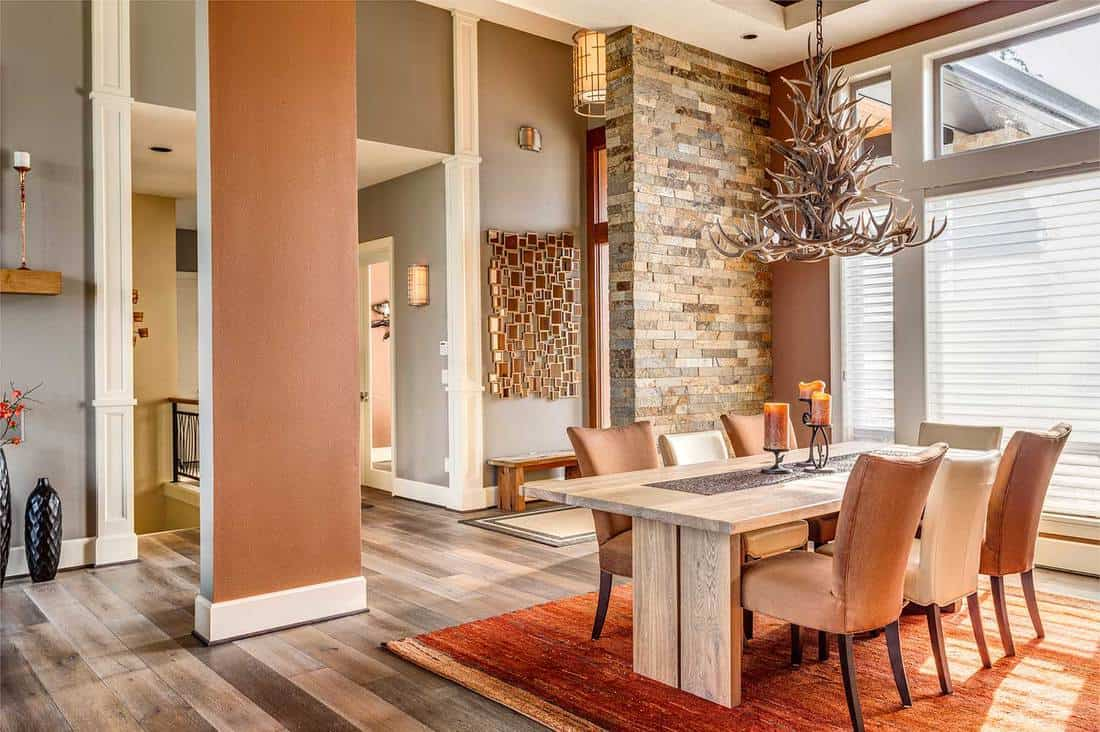 Luxury dining room with entryway, elegant light fixture, wooden table, hardwood floor and faux antler chandelier