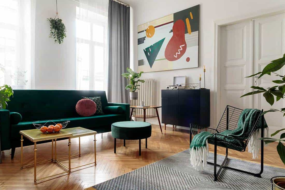 Luxury home interior with white walls, green sofa, parquet floor and wall art decor