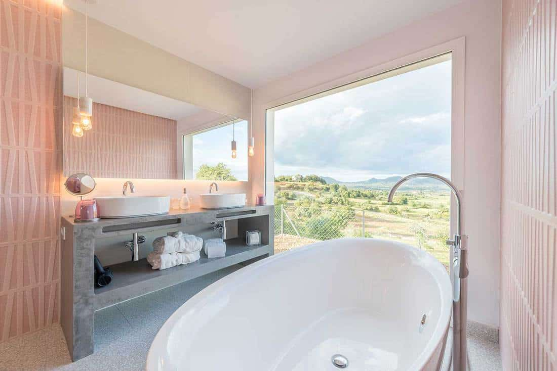 Luxury hotel bathroom with wonderful interior design and greenery view window