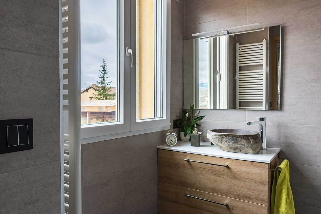 Modern and contemporary bathroom with stone wash basin by the window