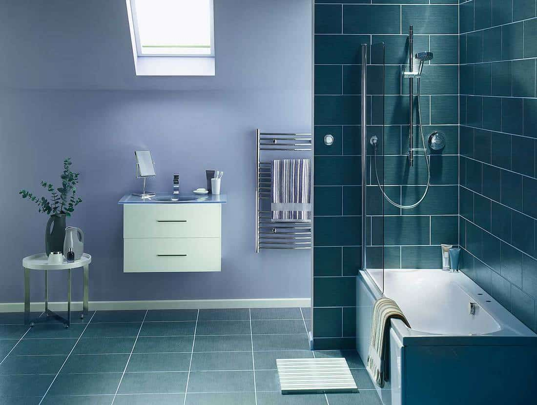 Modern bathroom in cool, blue-gray tone with sink, mirror, bathtub and shower