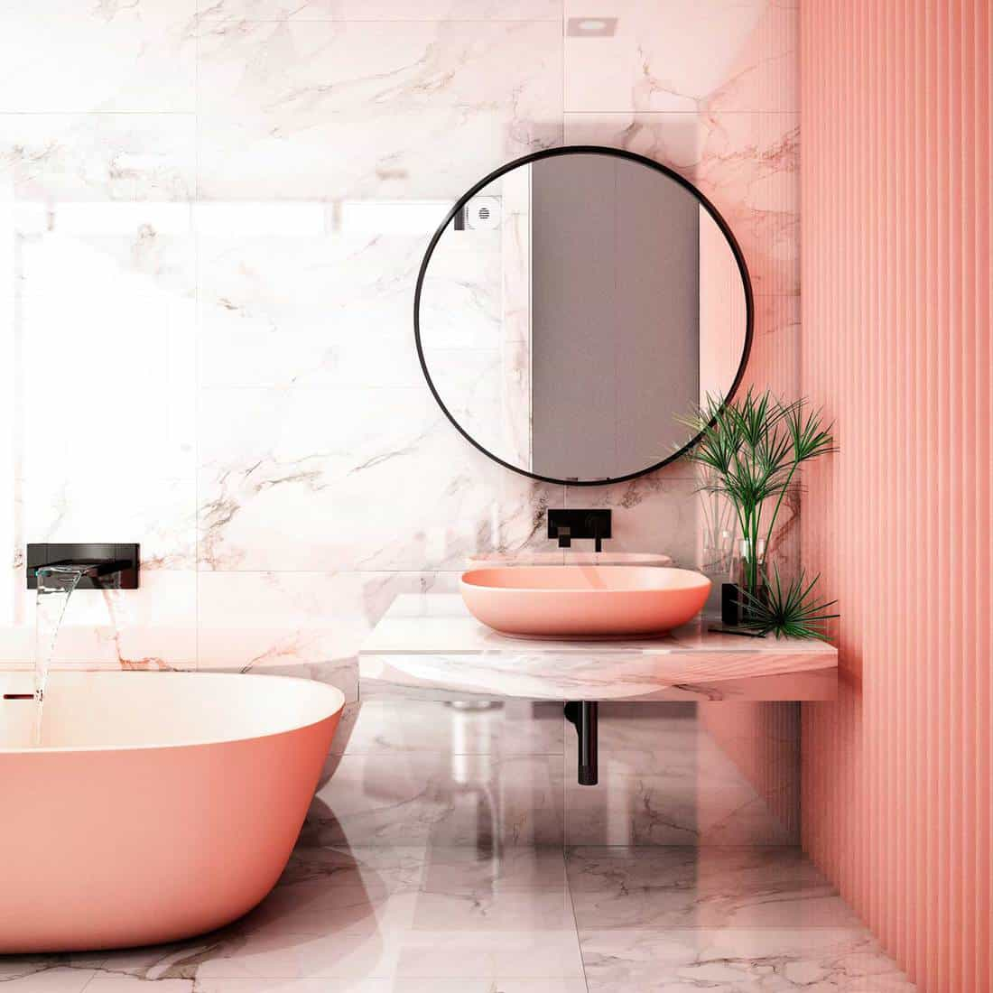 Modern bathroom interior with round mirror above pink wash basin, pink walls and pink bathtub